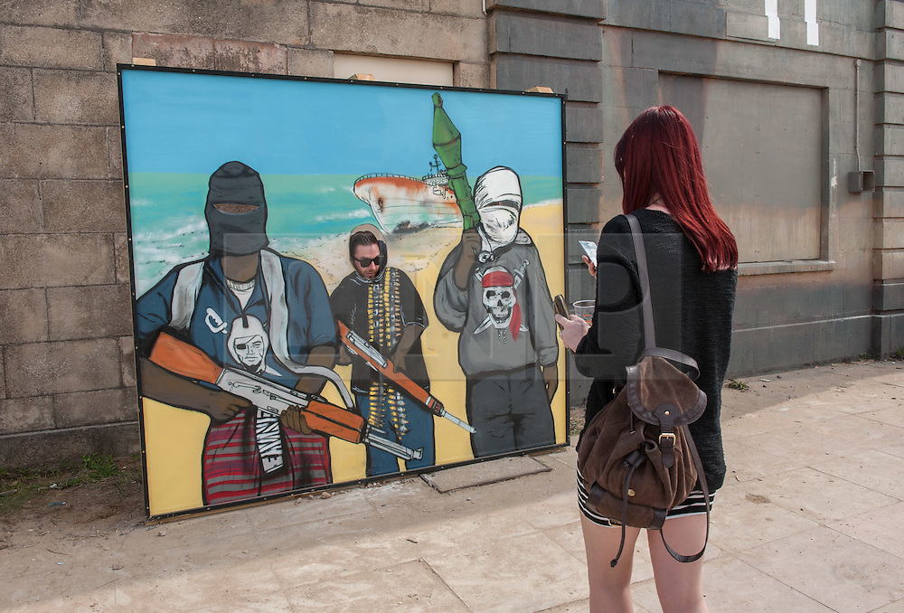 © Licensed to London News Pictures. 22/08/2015. Weston-super-Mare, North Somerset, UK.  Visitors pose for photos as terrorists on the first main day of BANKSY's Dismaland show at the old Tropicana on Weston seafront, when the event is open to the general public. Photo credit : Simon Chapman/LNP