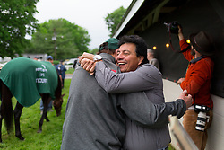 Kentucky Derby 142 winner Nyquist, left grazed while Team O'Neill assistant trainer Leandro Mora hugged operations team member Steve Rothblum at the undefeated colt's barn on the backside the morning after the race, Sunday, May 08, 2016 at Churchill Downs in Louisville.