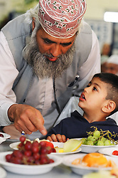 Father feeds his young son fruit at an Asian Health Promotion Day; Keighly; Yorkshire UK