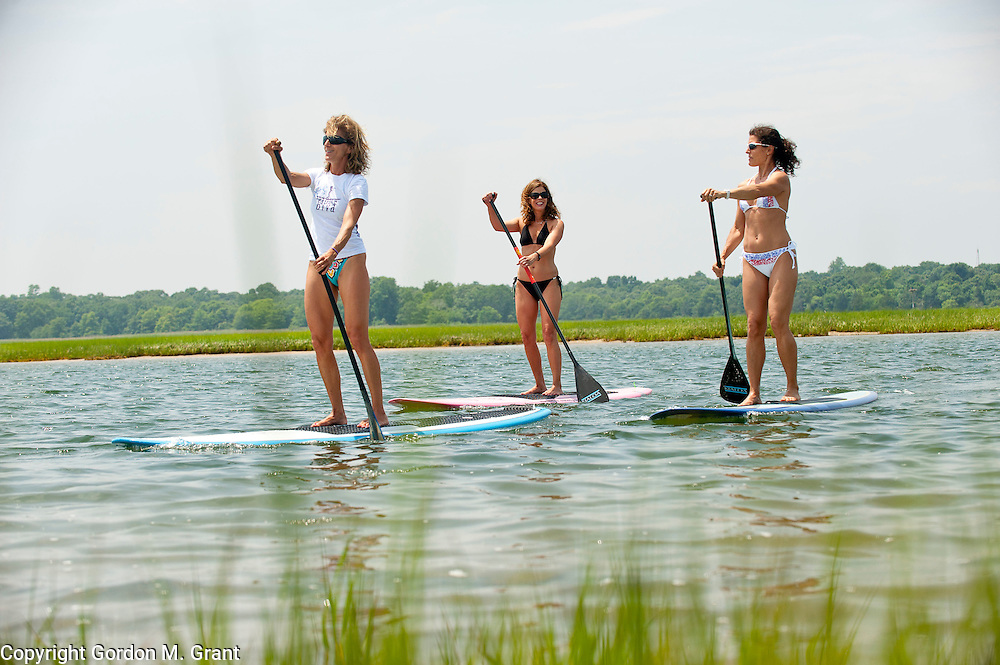 Gina Bradley, the owner of Paddle Diva, left, a paddleboard instructor, gives a lesson to (l-r) Meg Salen and Jennifer Ford at Louse Point in East Hampton.  (June 24, 2010)