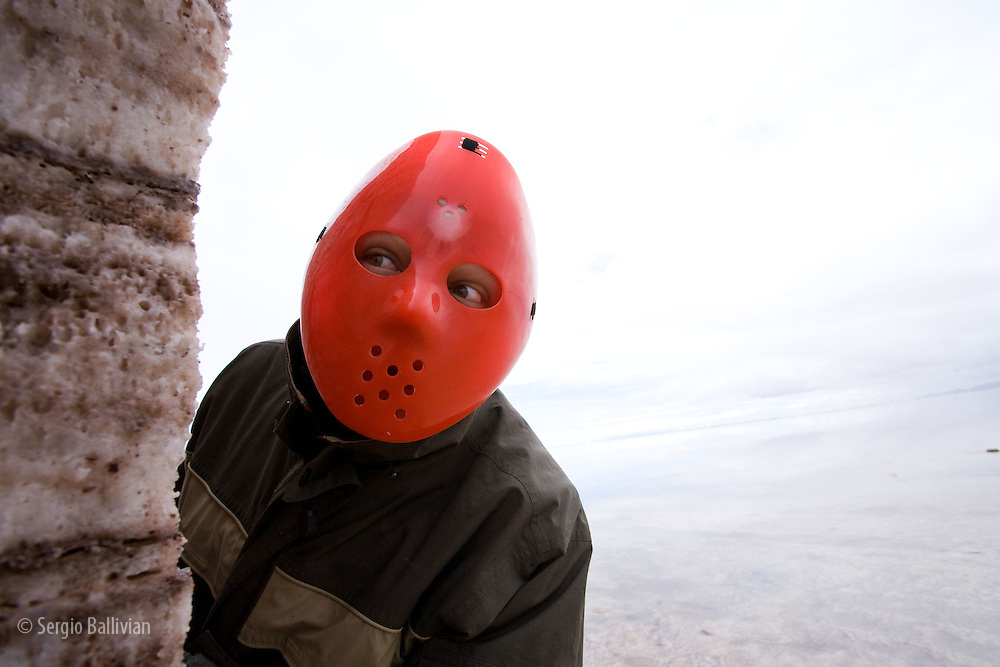 A man in a red hockey mask peeks around the corner of a wall.