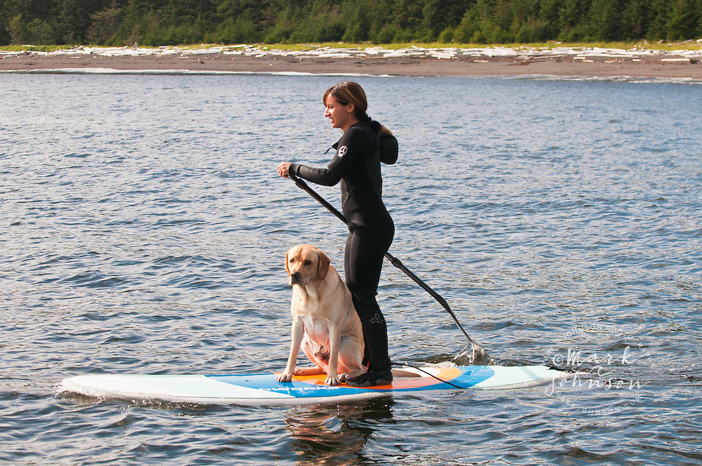 Woman & dog Standup Paddle Boarding off Kruzof Island, Southeast Alaska