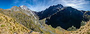Mount Awful (2192 m / 7190 ft, left) at the headwaters of the Young River, on the Track ascending Gillespie Pass, in Mount Aspiring National Park, Southern Alps, Otago region, South Island of New Zealand. UNESCO lists Mount Aspiring as part of Wahipounamu - South West New Zealand World Heritage Area. This image was stitched from multiple overlapping photos.