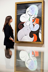 © Licensed to London News Pictures. 13/02/2012. LONDON, UK. A member of gallery staff looks at Pablo Picasso's 'Nude Woman in a Red Armchair' at a Tate Britain exhibition exploring the artist's lifelong connections with Britain. The exhibition, called 'Picasso and Modern British Art', starts at the Tate Britain on the 15th of February 2012. Photo credit: Matt Cetti-Roberts/LNP