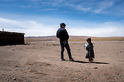 Tsetrim Yumden, 30, with his son outside their temporary home at the source of the Mekong rivert at Lasagongma Springs, Tibet (Qinghai, China). Tsetrim and his extended family act as volunteer guardians of the springs, which are the source of Asia's biggest rivers, and keep the area safe and free of trash.