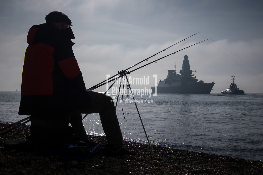 A man fishing as HMS Dragon sails into her home port of Portsmouth for the first time in two months.  The Type 45 destroyer has been on a deployment involving exercises with the U.S. Navy and also a visit to the British Overseas Territory of Gibraltar.