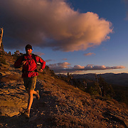 A picture of a man trail running at sunset in the mountains above Lake Tahoe California
