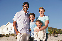 Family standing on beach smiling beach house behind