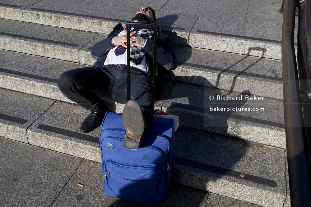 A tired traveller rests with his baggage in winter sunshine on the steps in Trafalgar Square, on 22nd January 2019, in London England.