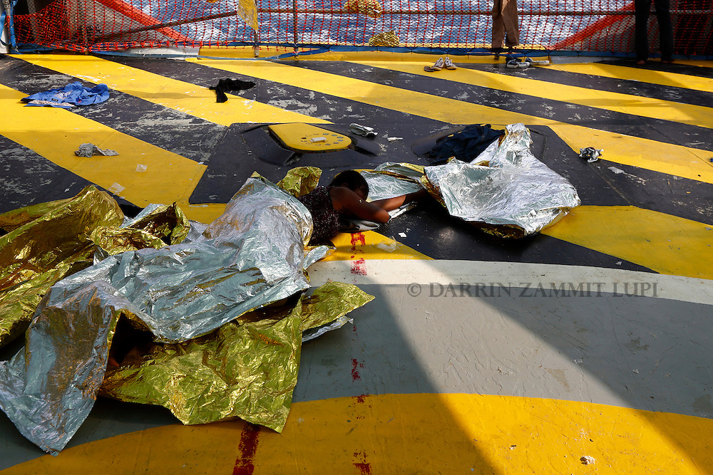 A migrant sleeps on the deck of the Medecins san Frontiere (MSF) rescue ship Bourbon Argos somewhere between Libya and Sicily August 8, 2015.  Some 241 mostly West African migrants on the ship are expected to arrive on the Italian island of Sicily on Sunday morning, according to MSF.<br /> REUTERS/Darrin Zammit Lupi <br /> MALTA OUT. NO COMMERCIAL OR EDITORIAL SALES IN MALTA