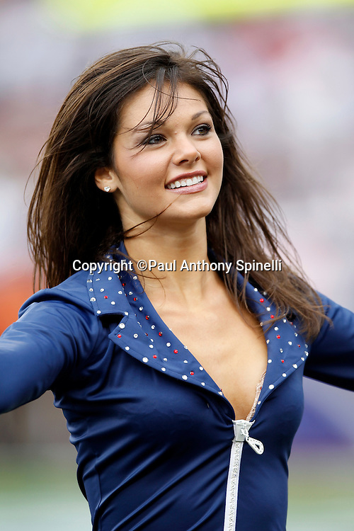 A New England Patriots cheerleader smiles during a dance routine at the NFL regular season week 3 football game against the Buffalo Bills on September 26, 2010 in Foxborough, Massachusetts. The Patriots won the game 38-30. (©Paul Anthony Spinelli)