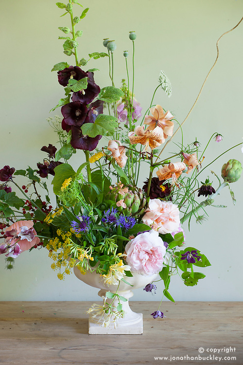 Charlie McCormick's flower arrangement<br /> Lily &lsquo;Tiger Babies&rsquo;, Rosa &lsquo;Aphrodite&rsquo; and &lsquo;Pretty Jessica&rsquo;, black hollyhock (Alcea nigra), with edibles &mdash; redcurrants and globe artichokes, and trailers, honeysuckle and clematis over the sides of the vase. Cosmos &lsquo;Daydream&rsquo;, sweet peas &lsquo;Wiltshire Ripple&rsquo; and &lsquo;Almost Black&rsquo; and poppy seed heads, dried and fresh