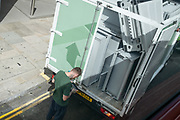 The driver of a van full of metallic items to be recycled, uses a delivery device at the rear of his vehicle, on 30th July 2020, in London, England.