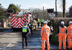 © Licensed to London News Pictures. 17/02/2018. Horsham, UK. Emergency workers and railway staff stand at a level crossing where two people have been killed near the village of Barns Green after a train hit a car. Photo credit: Peter Macdiarmid/LNP
