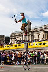 "London, July 18th 2015.  Canadian Unicyclist and juggler ""Dynamike"" entertains the crowd in Trafalgar Square as part of the Busk in London Festival aimed at showcasing the outstanding talents of many of the capital's finest street performers, including, musicians, magicians, living statues and bands."