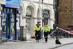 © Licensed to London News Pictures. 24/04/2019. London, UK. Police officers guard the crime scene on Harlesden High Street, Brent in West London where a 21 year old man was stabbed to death on Tuesday 23 April 2019 at about 9pm. The victim was pronounced dead at a hospital just before 3am on early this morning. Photo credit: Dinendra Haria/LNP