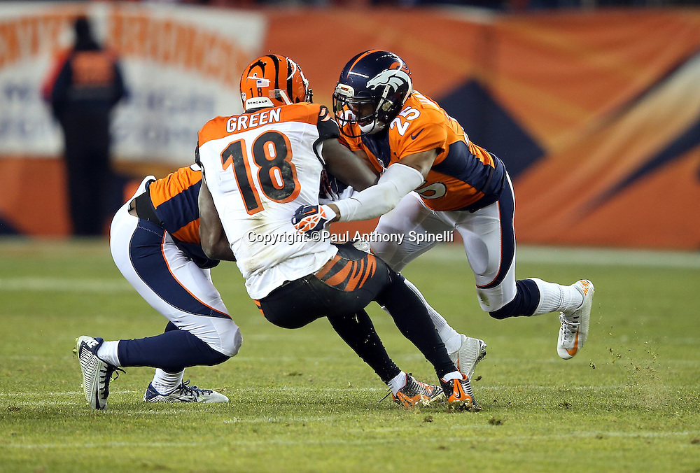 Cincinnati Bengals wide receiver A.J. Green (18) gets gang tackled by Denver Broncos cornerback Chris Harris Jr. (25) and a teammate after catching a pass during the 2015 NFL week 16 regular season football game against the Denver Broncos on Monday, Dec. 28, 2015 in Denver. The Broncos won the game in overtime 20-17. (©Paul Anthony Spinelli)