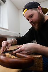Lee marks up an umbrella shaft ahead of cutting grooves for the retaining springs. Craftspeople at Fox Umbrellas Ltd, a company in Croydon, Surrey, that has been going for over 150 years hand build quality umbrellas. Croydon, Surrey, March 06 2019.