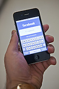 A man looks at the Facebook web site on his i-phone hand held device.
