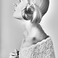 Female youth with hair tied in bun wearing white lace in profile