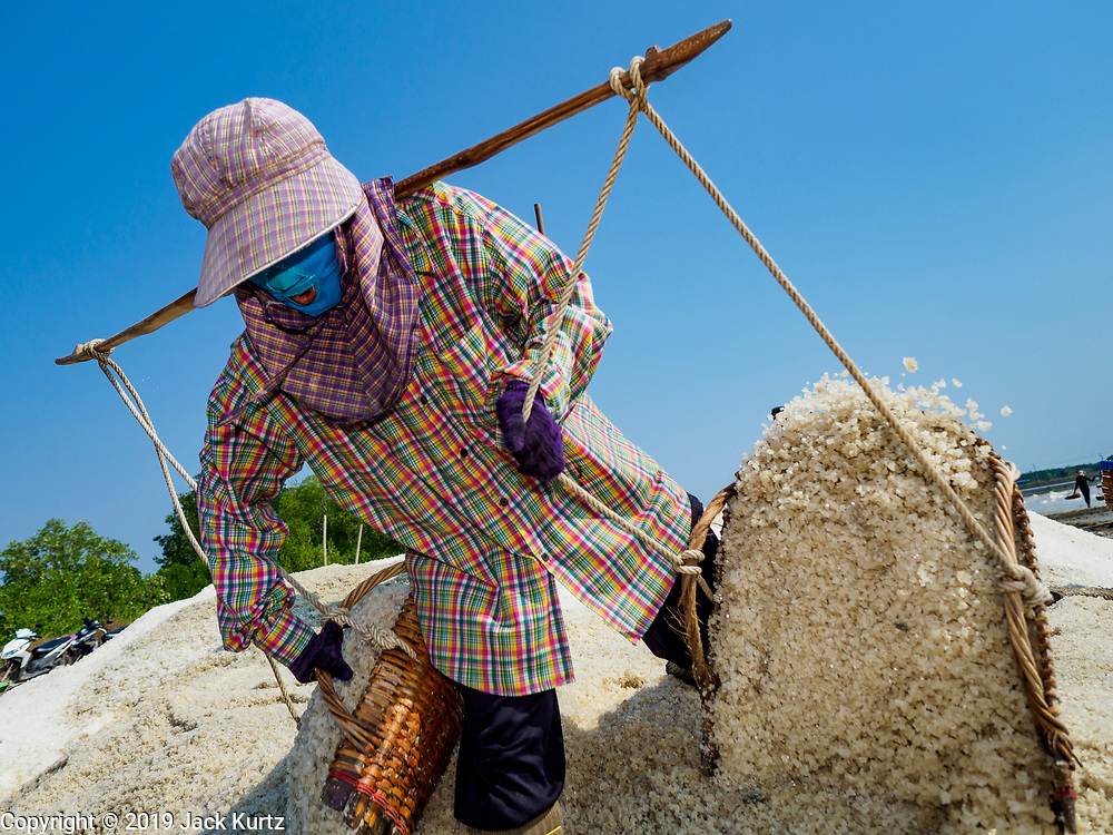 20 FEBRUARY 2019 - BAN LAEM, PHETCHABURI, THAILAND: A salt worker empties her baskets on a mound of salt on one of the first days of the 2019 salt harvest in Ban Laem, Thailand. Ban Laem's salt fields are expanding because salt harvesters in Samut Sakhon and Samut Songkhram,  which are closer to Bangkok, are moving to Ban Laem as their land is turned into industrial parks.     PHOTO BY JACK KURTZ