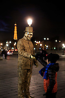 A young boy shakes the hand of a street performer, with the Eiffel Tower in the background, at the Place de la Concorde in Paris, France