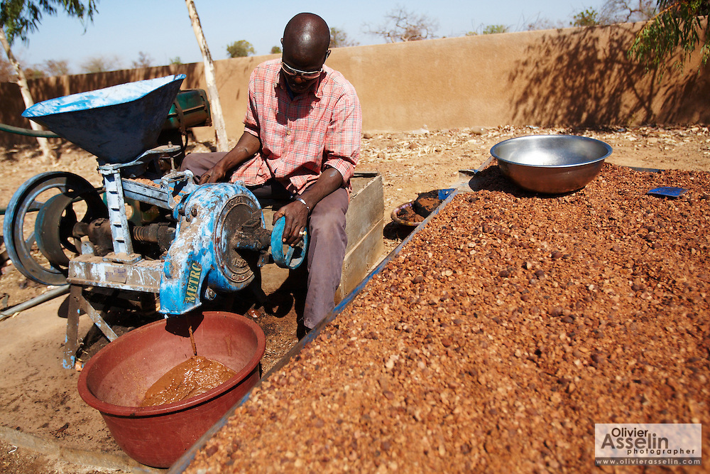 A man uses a machine to mill shea nut grounds into a paste at the Si Yiriwa shea processing center in the town of Diolila, Mali on Friday January 15, 2010.