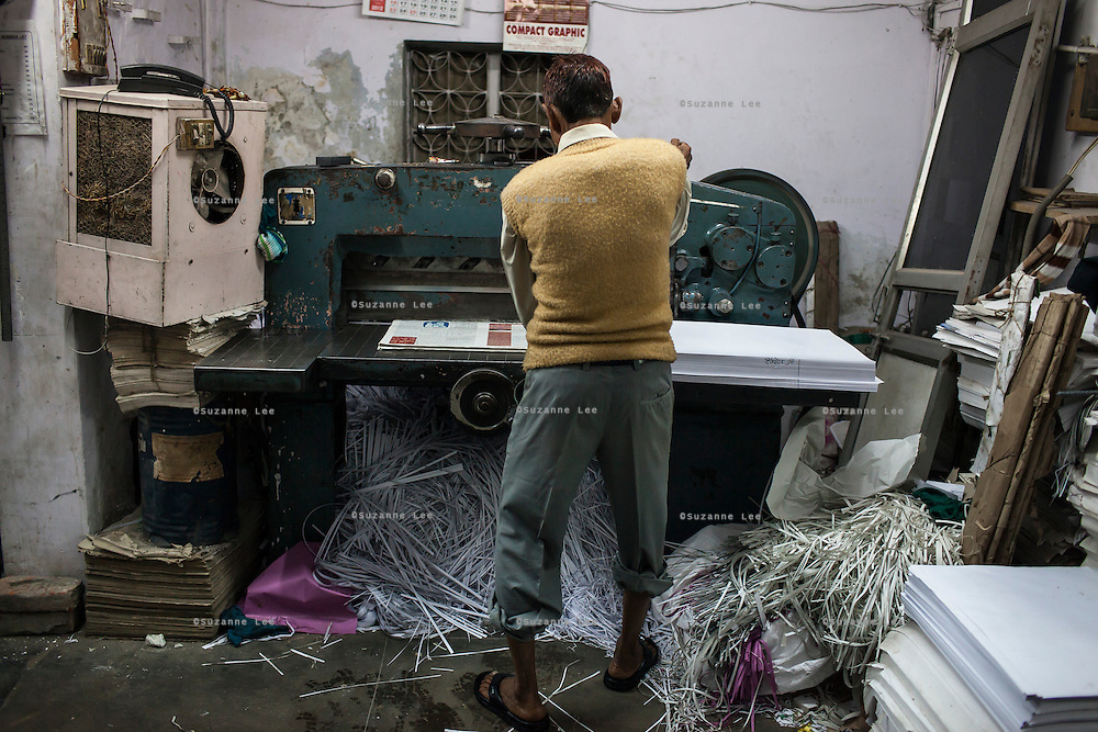 Workers cut the current issue of Khabar Lahariya weekly newspaper, after receiving the files from the newspaper's Chitrakoot office, in Allahabad, Uttar Pradesh, India on 06 December 2012. Photo by Suzanne Lee / Marie Claire France