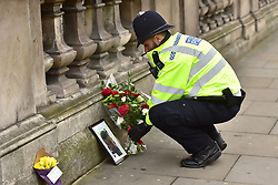 A police officer places flowers and a photo of Pc Keith Palmer on Whitehall near the Houses of Parliament in London, after seven people were arrested in raids in London, Birmingham and elsewhere linked to the Westminster terror attack.