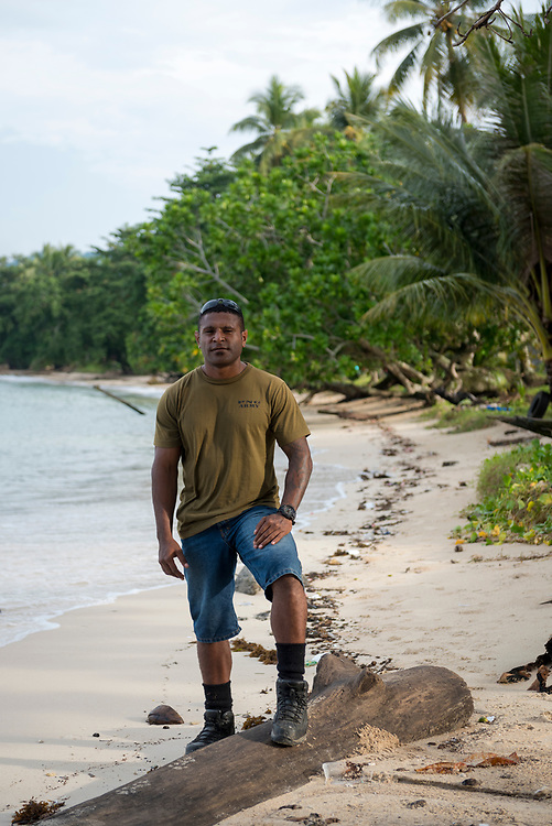 Clayton Yuwi, age 27 and a soldier in the Papua New Guinea Defence Force, stands on the beach outside his base in Vanimo, Papua New Guinea