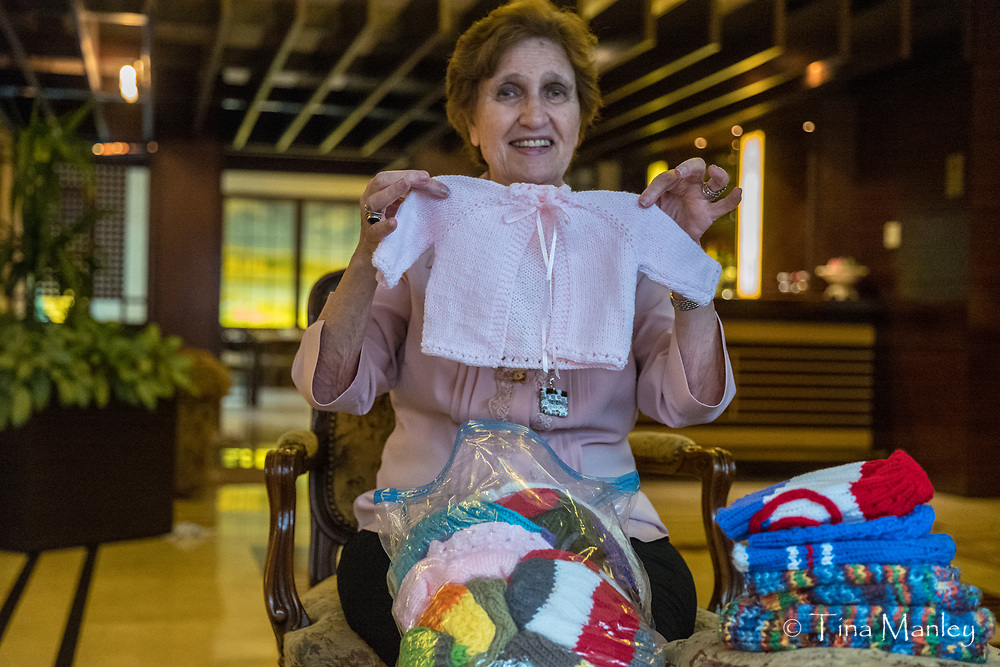 Sylvia Haddad, director of Beirut Palestinian and Syrian Refugee Camps receives donated knit goods.