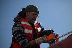 ATLANTIC OCEAN ABOARD ARCTIC SUNRISE 11MAY11 - Outboard mechanic Philip Dunn of Canada at work aboard the Arctic Sunrise......Photo by Jiri Rezac / Greenpeace