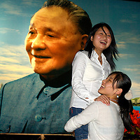 Young women playing around in front of a poster celebrating Deng Xiaoping as the father of the economic reforms that have transformed China.<br /> <br /> From China [sur]real &not;&copy; Mark Henley
