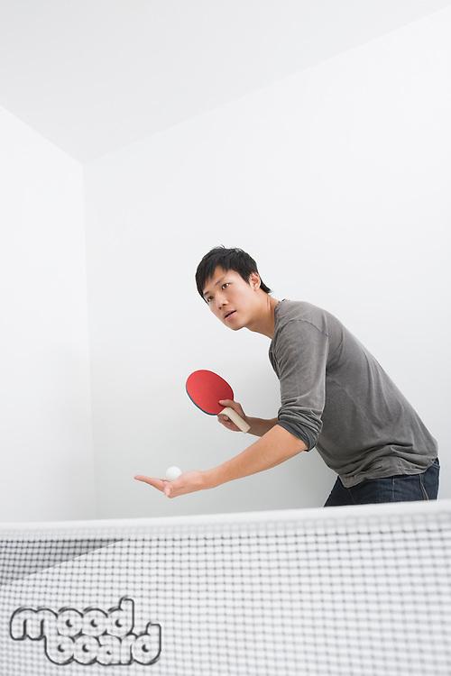 Mid adult man preparing to serve table tennis ball