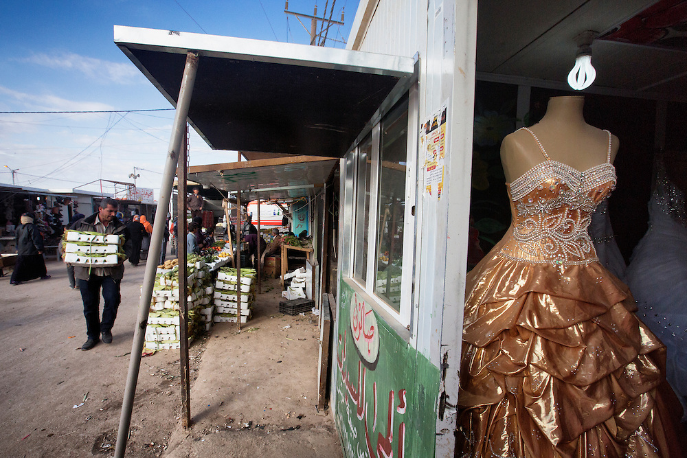 Life goes on in Zaatari. Here, a store sells dresses for the many weddings that take place every spring. Feb. 6, 2014. Zaatari Camp, Jordan. (Photo by Gabriel Romero/Alexia Foundation ©2014)