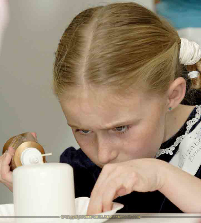 Elizabeth Brown, 8, who attends Waynesville Elementary adds her personal touches to a candle at the American Girl Tea Party, Saturday, January 27, 2007 in Waynesville's Mary L. Cook Library.