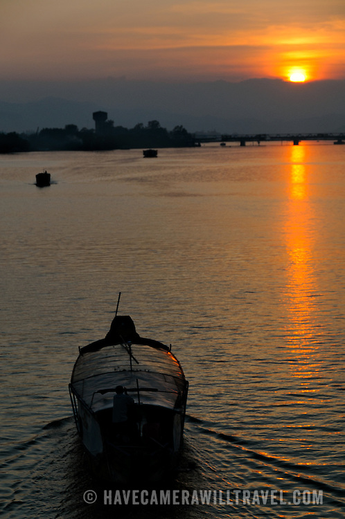 A boat makes its way up the Perfume River heading towards the setting sun.