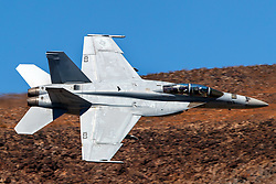 United States Navy Boeing F/A-18F Super Hornet (side 103) from the VFA-154 Black Knights squadron flies low level on the Jedi Transition through Star Wars Canyon / Rainbow Canyon, Death Valley National Park, Panamint Springs, California, United States of America