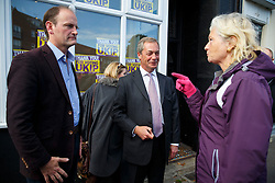 © Licensed to London News Pictures. 10/10/2014. Clacton, UK. Douglas Carswell, newly elected and first ever MP of UKIP for Clacton-on-Sea and UKIP leader Nigel Farage talking to a member of public whilst leaving UKIP campaign office in Clacton town centre on Friday, 10 October, 2014 after their victory in the by-election of Clacton-on-Sea. Photo credit : Tolga Akmen/LNP