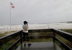 October 10, 2018 - Panama City, Florida, U.S. - A woman takes pictures in the city pier early morning prior to the Hurricanes arrival in Panama City Beach. Hurricane Michael made landfall just east of Panama City, Florida on Wednesday with pounding 155 mph winds, just shy of a Category 5 storm. (Credit Image: © Pedro Portal/Miami Herald/TNS via ZUMA Wire)