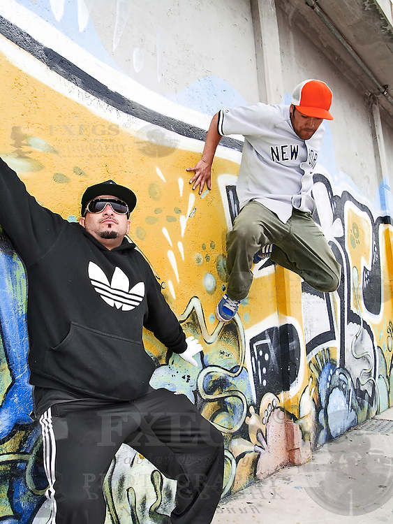 Two hip-hop men in a composition with a graffited wall
