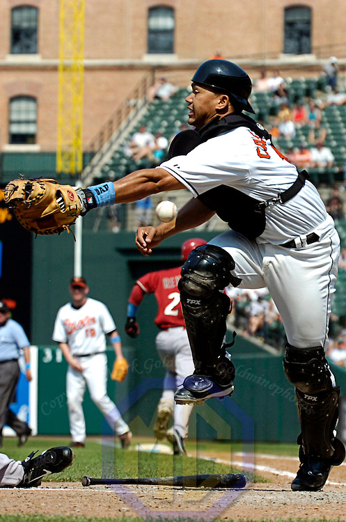 17 June 2007:  Baltimore Orioles catcher Alberto Castillo (R) cannot come up with a errant throw from second baseman Brian Roberts that allows Arizona Diamondbacks left fielder Scott Hairston to score the winning run in the 8th inning.  The Diamondbacks defeated the Orioles 6-4 in inter-league play to sweep the three game series at Camden Yards in Baltimore, MD.   ****For Editorial Use Only****