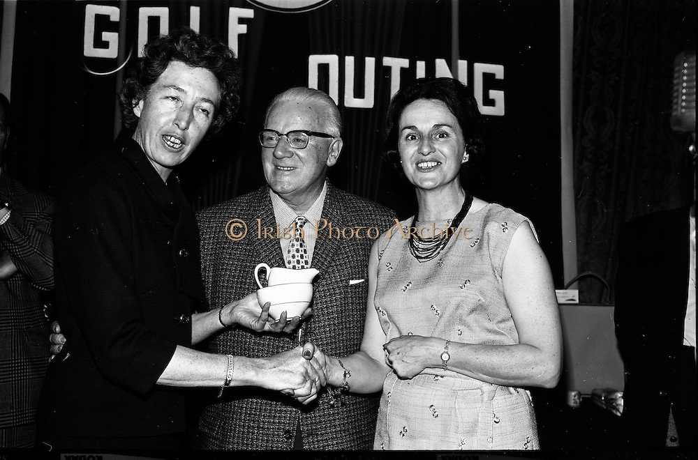 14/05/1965<br /> 05/14/1965<br /> 14 May 1965<br /> Esso Golf Outing at Woodbrook Golf Club, Bray, Co. Wicklow. Mrs J.H. Donovan, (right) wife of the Managing Director of Esso, presenting the Ladies prize to Miss Monica Mullins, Secretary to Managing Director. In centre is Mr Mr T.F. Laurie, Director Esso.