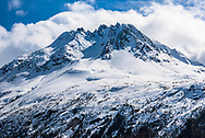 A snow capped mountain peak in the Skagway mountains with a blue sky background.