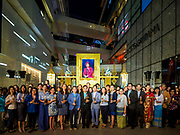 12 AUGUST 2018 - BANGKOK, THAILAND: Thais stand in front of a portrait of the Queen Mother after a candlighting ceremony to honor the 86th birthday of Sirikit, the Queen Mother of Thailand at EmQuartier Mall in Bangkok. She was the wife of Bhumibol Adulyadej, the late King, and she is the mother of His Majesty King Maha Vajiralongkorn Bodindradebayavarangkun of Thailand, who succeeded his father. August 12 is also celebrated as Mother's Day in Thailand.     PHOTO BY JACK KURTZ
