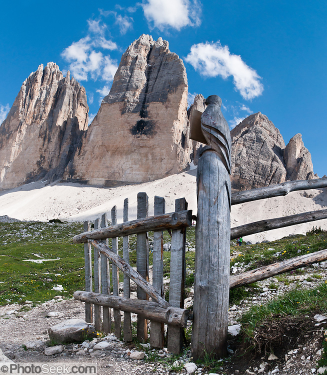 "A carved bird decorates a gate. Hike for spectacular views around Tre Cime di Lavaredo (Italian for ""Three Peaks of Lavaredo,"" also called Drei Zinnen or ""Three Merlons"" in German), which are distinctive icons of the Alps, in the Sexten Dolomites of northeastern Italy, Europe. Until 1919 the peaks formed part of the border between Italy and Austria. Now they lie on the border between the Italian provinces of South Tyrol and Belluno and still are a part of the linguistic boundary between German-speaking and Italian-speaking majorities. Cima Grande rises to 2999 meters (9839 feet), between Cima Piccola  2857 m (9373 ft) and Cima Ovest  or ""Western Peak"" 2973 m (9754 ft). The Dolomites were declared a natural World Heritage Site (2009) by UNESCO. Panorama stitched from 2 overlapping photos."