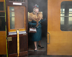 © Licensed to London News Pictures. <br /> 16/10/2016. <br /> Grosmont, UK.  <br /> <br /> ELISABETH TIMM from Bridlingtpn stands looking from the train carriage door at Grosmont station during the final day of the North Yorkshire Moors Railway Wartime Weekend event.   <br /> The annual event brings together re-enactors and enthusiasts along the length of the NYMR heritage steam railway line to recreate the feel of the war years of the 1940's. <br /> <br /> Photo credit: Ian Forsyth/LNP