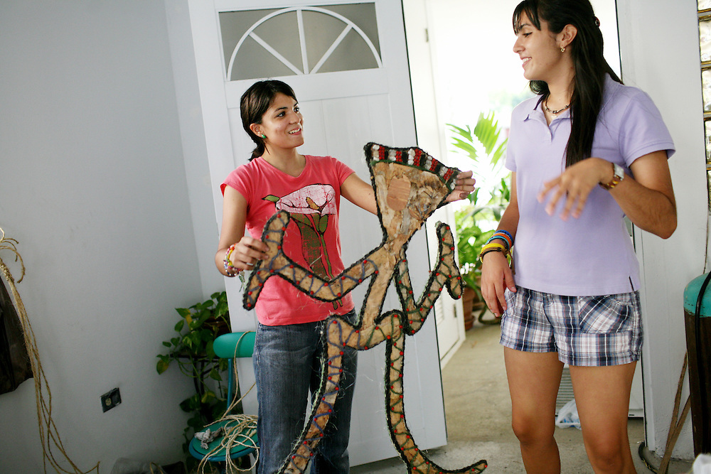 "Natalia Fernandez, 16, left, with friend Nicole Rivera, 16, right, prepares her costume for the Taino pageant, called a reinado, for the 39th annual Festival Indigena de Jayuya, which honors their Taino Indian heritage, in Jayuya, Puerto Rico, on Tuesday, November 18, 2008. Each contestant, nominated by their classmates from each school, will be judged by their costume design and native look. This year's festival is based on Taino musical instruments, and Fernandez named her costume, ""El Danzante del Sonido,"" the sound dancer in Spanish."