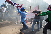 CHARLOTTESVILLE, USA - August 12: A White Supremacist tries to strike a counter protestor with a White Nationalist flag during clashes at Emancipation Park where the White Nationalists are protesting the removal of the Robert E. Lee monument in Charlottesville, Va., USA on August 12, 2017.