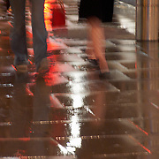 Man and women walking in rain storm at night on sidewalk, Kensington High Street, Kensington, London, England, UK<br />